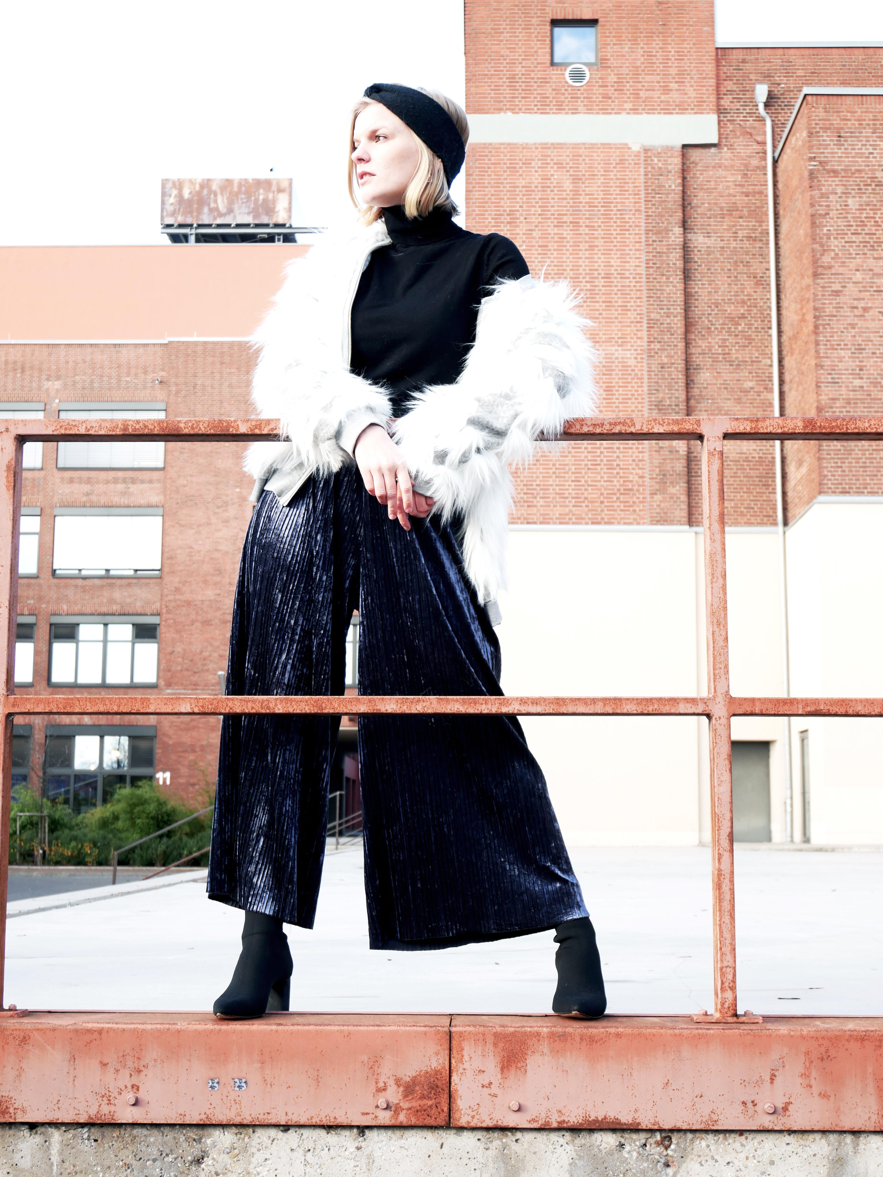 0e72e6518fe7d2 Crew Member Isabell wagt sich an eine außergewöhnliche Materialkombination.  Sie stylt ihre Fake Fur Jacke zu einer schimmernden Culotte in Samtoptik  und ...
